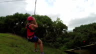Young girl smiling, screaming and having fun while zipling above lush rainforest video