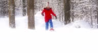 Young girl Snowshoeing through deep powder snow in the forest video