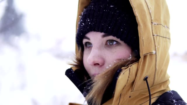 Young girl standing under snow in the park. The girl is wearing winter closes, her face, hands, and hair are covered with snow and she smiles happily video