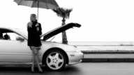 Young girl stands beside a broken car under the umbrella waiting for help video
