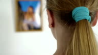 Young girl staring at photo of a little girl in frame hanging on the wall video