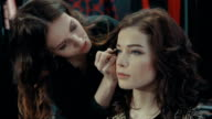 A young girl stylist puts on the eyelids of a brunette model with an eyeliner. video