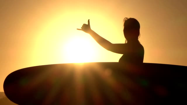 CLOSE UP: Young girl surfer holding longboard, doing surfers shaka sign gesture video