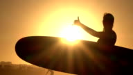 CLOSE UP: Young girl surfer holding surfboard, doing surfers shaka sign gesture video