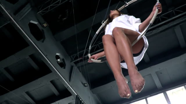 Young girl sways in the aerial hoop in slowmotion video