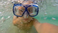 Young girl swimming underwater wearing a mask video