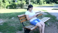 young girl touching smartphone in the park video