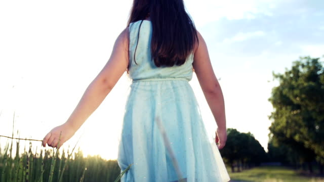 Young Girl Walking at Sunset Through Tall Grass video