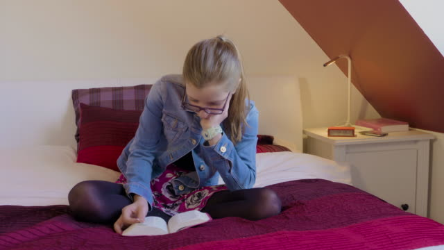 Young girl wearing glasses sitting on bed reading a book. video