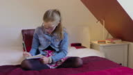 Young girl wearing glasses sitting on bed writing on a notepad. video