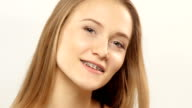 Young girl with braces on teeth looking at camera and smiling. White video