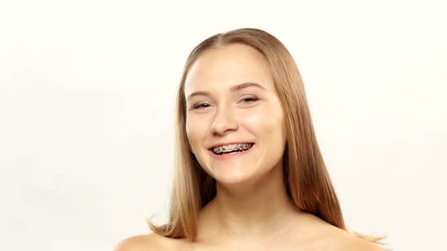 Young girl with brackets on teeth watch and blinking. White video