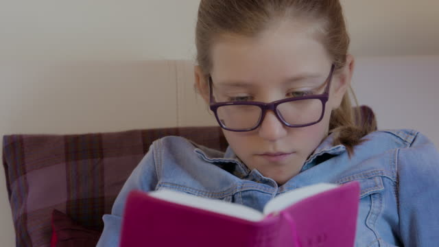 Young girl with glasses reading a book in bed. video