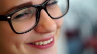 Young girl with glasses, smiling. Close-up video