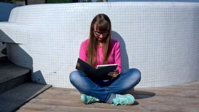 Young girl with her tablet pc outside video