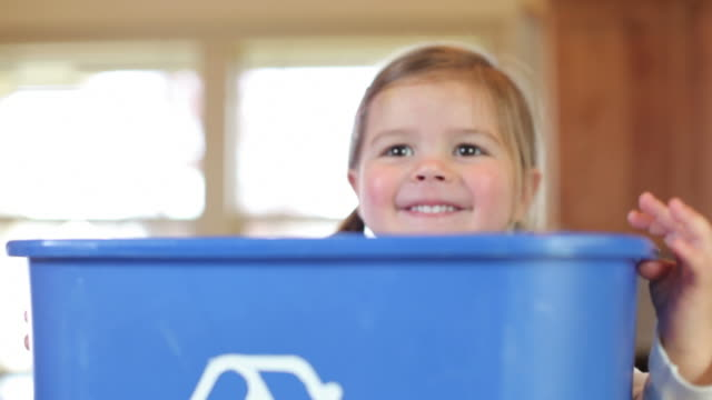 Young girl with recycle bin smiling video