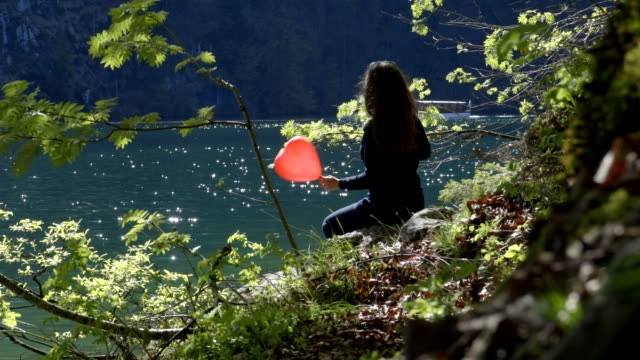 Young girl with red balloon in shape of heart in nature. video