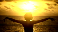 Young girl with short hair, wearing a T-shirt, raises his hands up against the yellow sunset near the ocean video