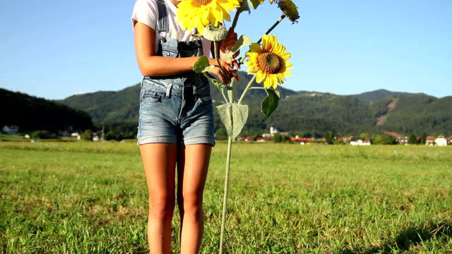 Young girl with sunflowers at sunset video