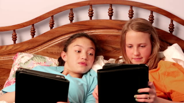Young girlfriends in bed using their tablets video