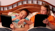 Young girlfriends in bed with pet dog using their tablets video