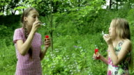 Young girls blowing soap bubbles outdoor video