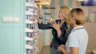 Young girls choosing new nail polish tone at cosmetic shop, best friends in supermarket video