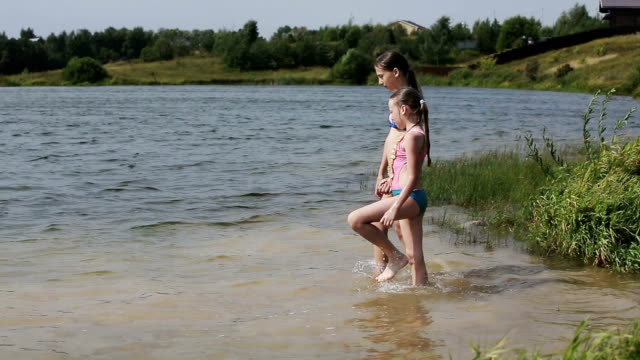 Young girls go into the water of the lake video