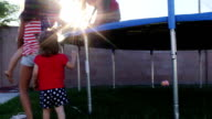 Young Girls Help Each Other Climb Onto a Trampoline video