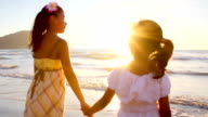 Young girls hold hands on a Mexican beach at sunset video