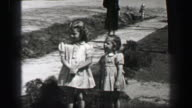1939: Young girls in formal dress with wavy curly long bangs hair style. video