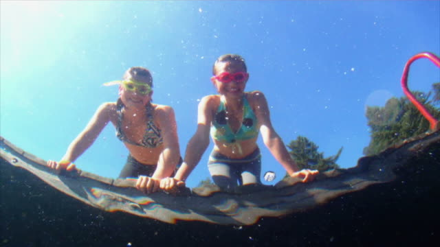 Young girls looking into water from swim platform video
