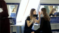 Young girls prepare for photoshoot in dressing room in day time video