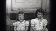 1939: Young girls sitting front porch stoop with wavy curly long bangs hair style. video