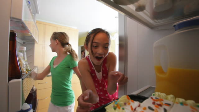 Young girls steal birthday cake from refrigerator video