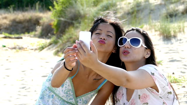 Young girls take selfie on the beach- slowmotion video