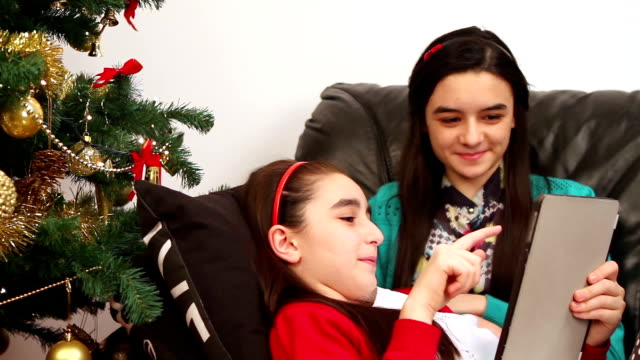 Young girls using a digital tablet near Christmas tree video