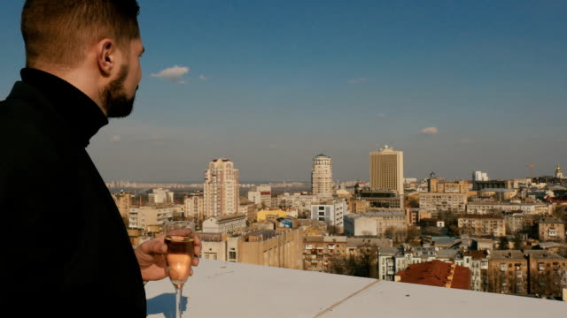 Young guy drinks the champagne on the roof video
