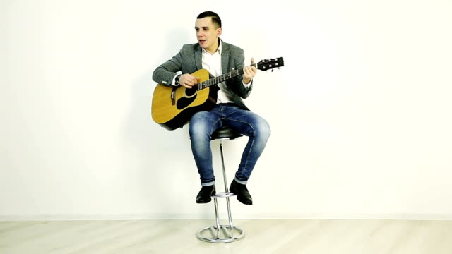 A young guy in a jacket sits on a bar stool and plays an acoustic guitar. video