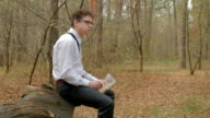 Young guy in glasses relaxing in the forest and eating the sandwich video