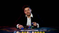 Young guy in the online casino at the gaming table. Close up video