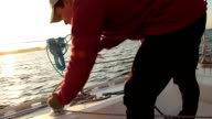 Young guy sailor securing rope on sailboat, work, occupation video