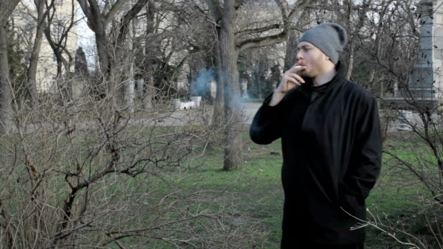 Young guy smokes cigarette at street video
