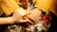 A young hand comforting a old pair of hands. video