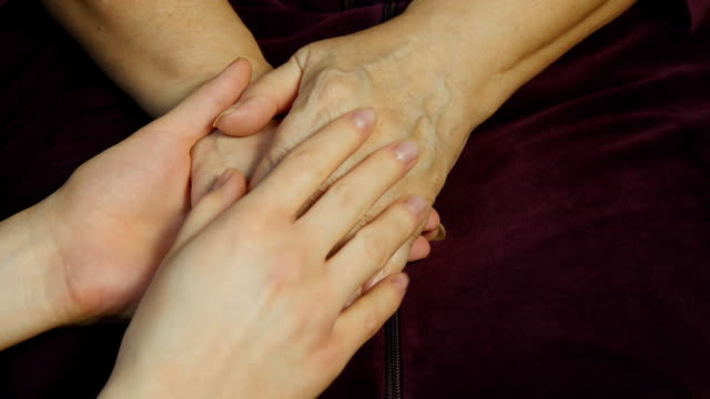 A young hand comforting an elderly pair of hands video