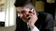 Young handsome businessman talking at the smart phone video