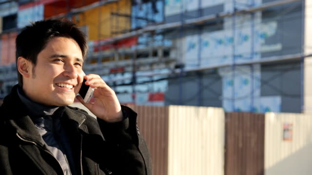 Young handsome businessman talking on a smartphone near the unfinished modern building in the winter video