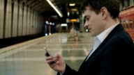 Young handsome businessman texting on cell in subway video