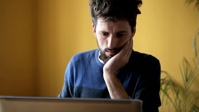 Young handsome hipster bearded man working in office on laptop video
