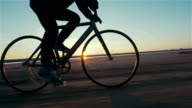 Young handsome hipster man riding fixed gear bicycle during sunset, outdoor video